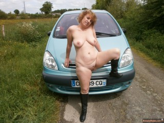 French Nudist Woman Posing on Car Outdoors